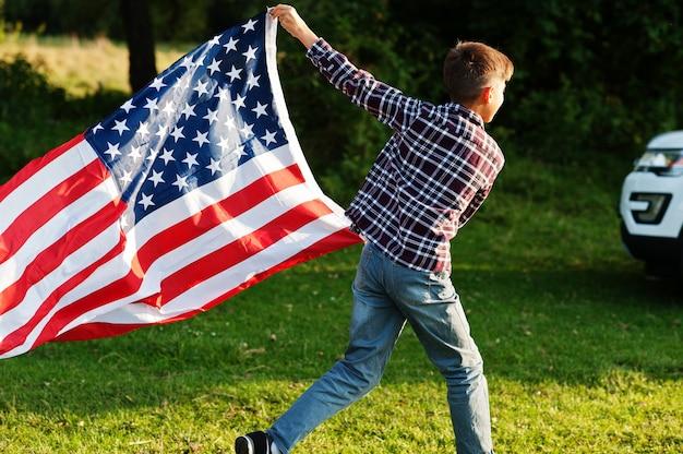 Ragazzo con bandiera usa all'aperto. l'america festeggia.