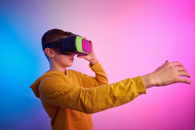 Ragazzo con occhiali per realtà virtuale sullo sfondo colorato