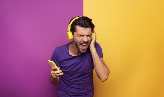 Il ragazzo con la cuffia avricolare gialla ascolta musica e balli. espressione emotiva ed energetica