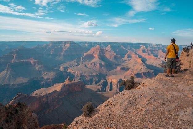 Un ragazzo con una maglietta gialla che si gode la vista del tramonto a mojave point nel grand canyon