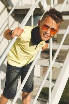 Il ragazzo in una maglietta gialla si siede sulle scale con gli occhiali da sole