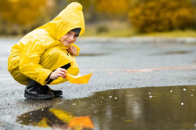 Ragazzo in mantello impermeabile giallo e stivali di gomma neri che giocano con il giocattolo barca fatto a mano di carta in una pozzanghera all'aperto sotto la pioggia in autunno.