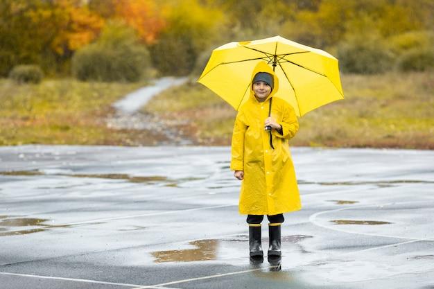 Ragazzo in mantello impermeabile giallo e stivali di gomma neri in piedi in una pozzanghera all'aperto sotto la pioggia in autunno.
