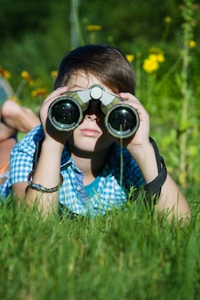 Giovane ricercatore del ragazzo che esplora con l'ambiente del binocolo in giardino verde