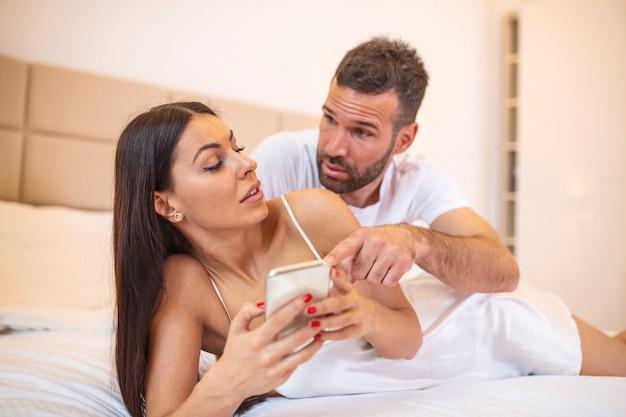 Fidanzato che chiede una spiegazione alla sua ragazza triste imbroglione seduta sul letto, indicando il suo telefono cellulare