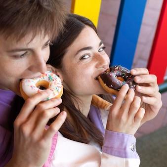 Ragazzo e ragazza che mangiano ciambelle all'aperto