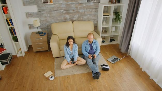 Fidanzato e fidanzata che giocano ai videogiochi con il controller wireless.