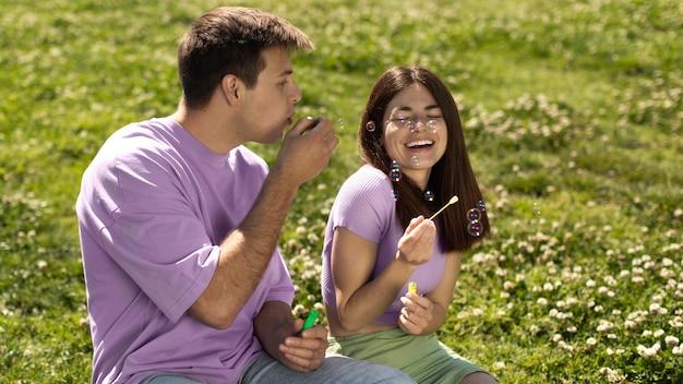 Ragazzo e ragazza che giocano con le bolle di sapone