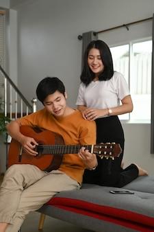 Un ragazzo sta suonando la chitarra per la sua bellissima ragazza sul divano del soggiorno