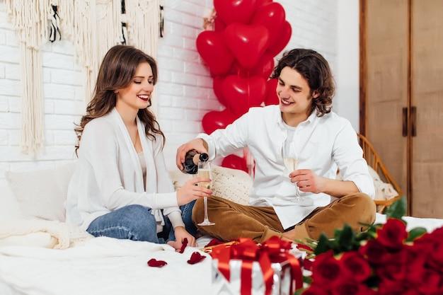 Fidanzato che versa champagne nel bicchiere per la fidanzata, celebrando san valentino a casa