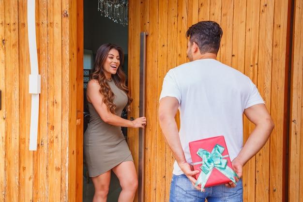 Fidanzato che visita la sua ragazza e fa una sorpresa con le mani dietro nascondendo il regalo mentre lei apre la porta per fargli entrare.