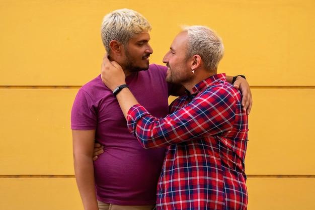 Fidanzati che si abbracciano vicino al muro giallo