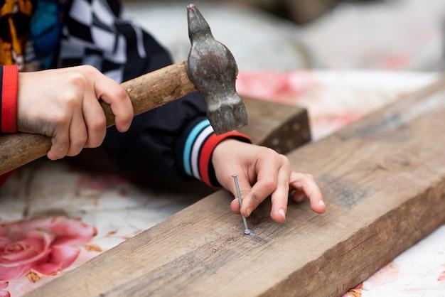 Le mani dei ragazzi tengono un martello e piantano un chiodo nella tavola