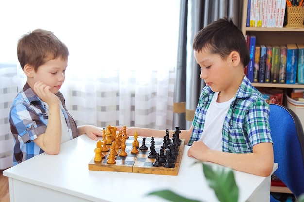 I ragazzi giocano a scacchi a casa. concetto di svago in quarantena di isolamento. il fratello maggiore insegna al minore a giocare a scacchi