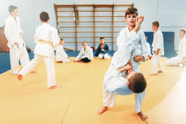 Ragazzi in kimono combattono, kid judo training. giovani combattenti in palestra, arti marziali per la difesa