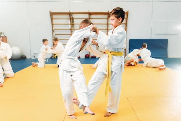 Ragazzi in kimono combattono, kid judo training