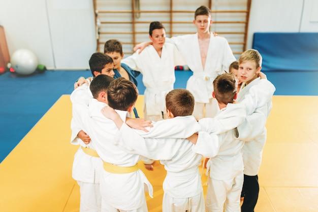 Ragazzi in kimono su kid judo training indoor. giovani combattenti in palestra, arti marziali per la difesa