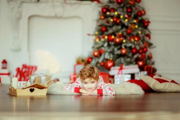 Ragazzi sdraiati su un tappeto di pelliccia naturale in pigiama rosso sotto l'albero di natale
