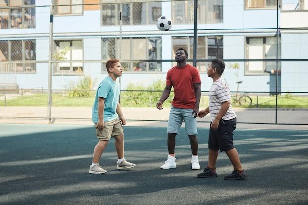 Ragazzi che giocano a calcio al parco giochi
