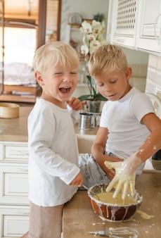Ragazzi che preparano la torta fatta in casa in cucina. due fratelli cooki