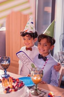 Ragazzi che indossano cappelli da festa davanti a una deliziosa torta