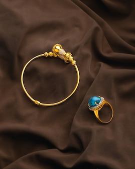 Bracciale e anello d'oro su tessuto sfilacciato