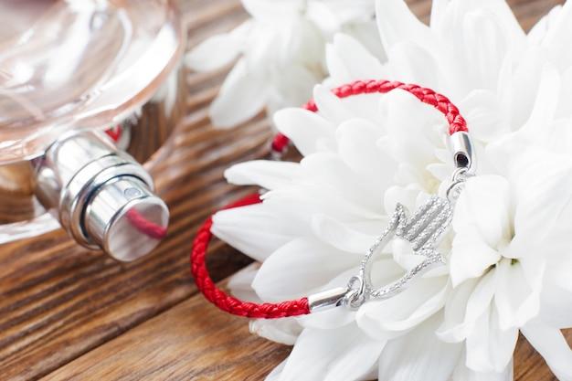 Bracciale su fiore bianco e profumo. bellissimo sfondo morbido con il primo piano di accessori femminili. composizione romantica del personale femminile