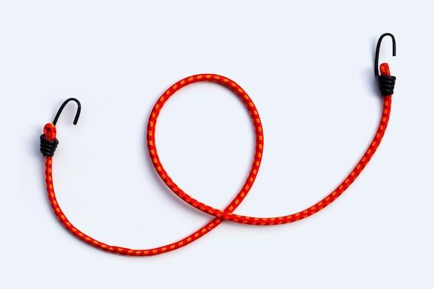 Cinghia elastica intrecciata con ganci su fondo bianco.