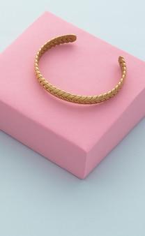 Braccialetto dorato intrecciato su scatola rosa su sfondo blu con copia spazio