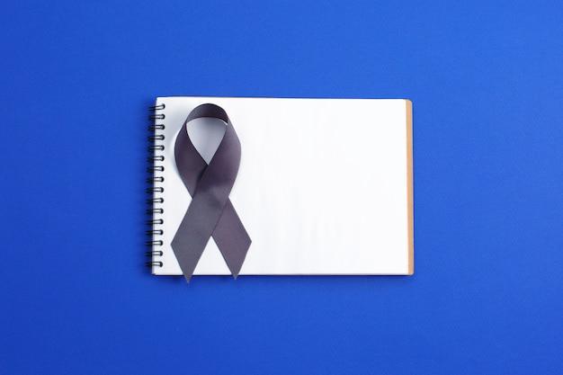Nastro di consapevolezza di colore grigio del cancro al cervello isolato su fondo blu