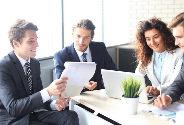 Brainstorming. gruppo di uomini d'affari che guardano insieme il laptop. una donna d'affari che guarda l'obbiettivo.