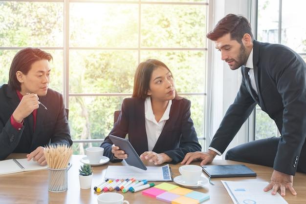 Brainstorm con i colleghi multietnici di affari. la donna asiatica di affari tiene il tablet con il suo team di affari in ufficio.