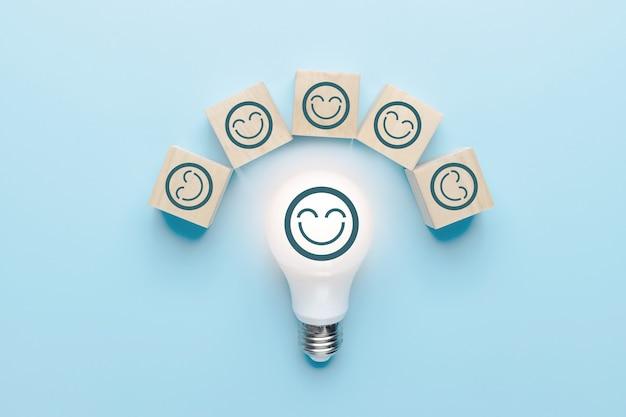 Brainstorming e concetto di squadra di idee creative, lampadina con la faccia dell'icona sorridente e blocco di legno su sfondo blu