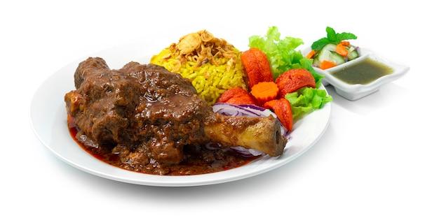 Stinco di agnello brasato riso biryani ricetta massaman curry tenero e sminuzzabile spezie indiane e cucina thailandese stile fusion all'interno del piatto con salsa alla menta vista laterale