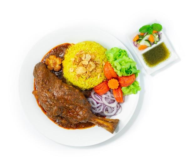 Stinco di agnello brasato riso biryani ricetta massaman curry tenero e sminuzzabile spezie indiane e cibo tailandese stile fusion all'interno del piatto con salsa alla menta vista dall'alto