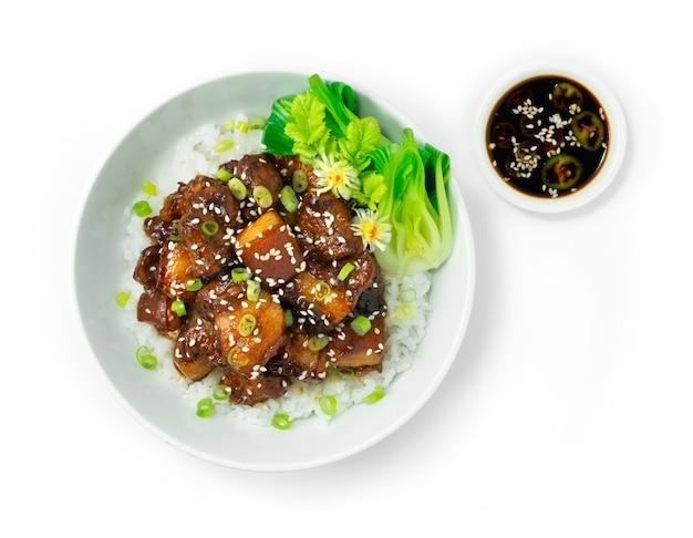 Pancia di maiale brasata caramellata su ricetta di riso cospargere con cipolla primavera e sesamo decorare le verdure servite salsa di fagioli di soia nera vista dall'alto in stile cinese