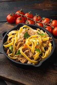 Coniglio brasato con rosmarino, aglio e tagliatelle di pasta o set di pappardelle, in padella o pentola di ghisa, sul vecchio tavolo di legno scuro