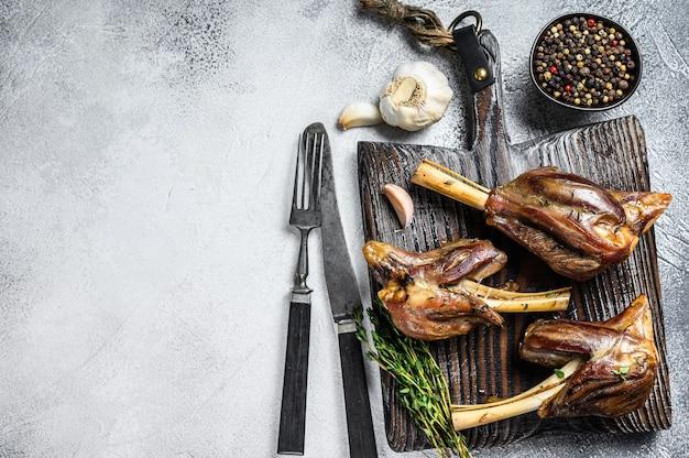 Stinco di agnello arrosto brasato su un tagliere di legno. tavolo bianco. vista dall'alto. copia spazio.