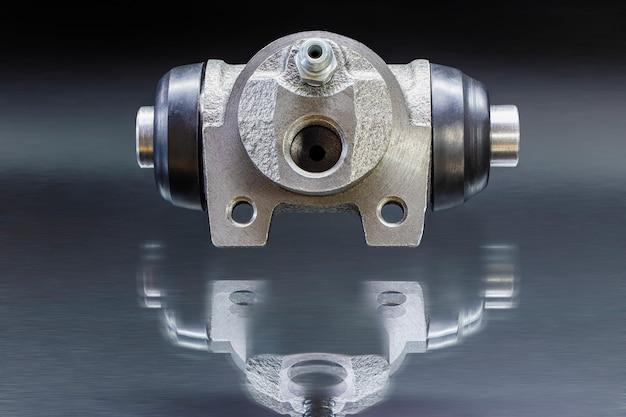 Tamburo del freno del cilindro idraulico del freno con riflessi sulla superficie su uno sfondo nero