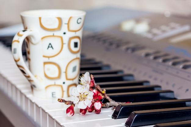 Ramo di albicocca con fiori e una tazza di caffè caldo sui tasti del pianoforte