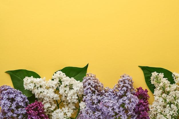 Ramo di bellissimo lilla bianco su sfondo giallo. vista dall'alto. biglietto di auguri festivo con lilla per matrimoni, felice festa della donna san valentino e festa della mamma.