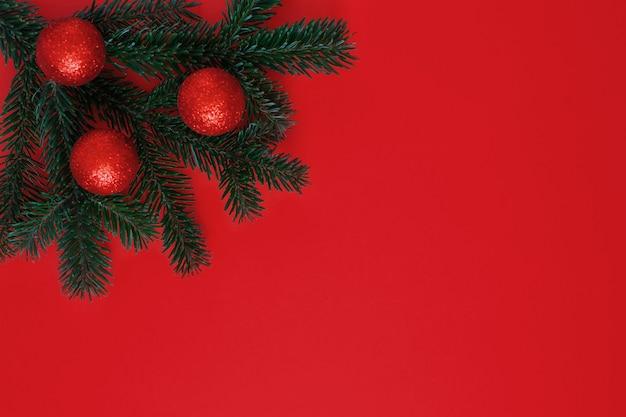 Un ramo di un albero di abete con palle di giocattoli di natale e capodanno su uno sfondo rosso per cartoline di natale e saluti.