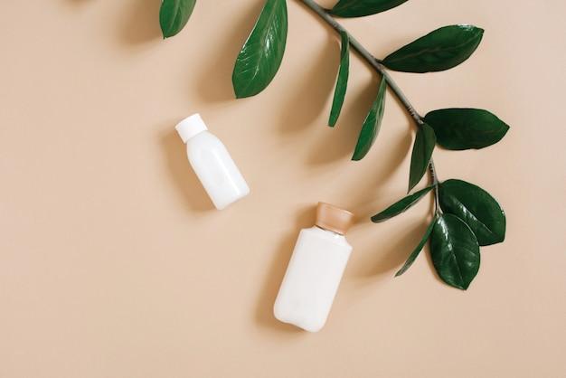 Un ramo della pianta tropicale verde zamiokulkas e bottiglie di cosmetici biologici, crema per il corpo o crema per il viso. cosmetici a base di erbe per la bellezza