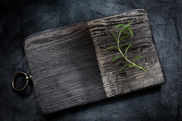 Ramo di rosmarino su un tagliere di legno su sfondo scuro