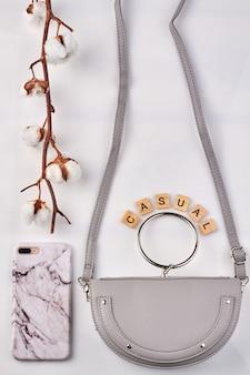 Ramo di cotone bianco vicino a cose alla moda. elegante borsa in pelle e cassa del telefono in marmo su sfondo bianco.