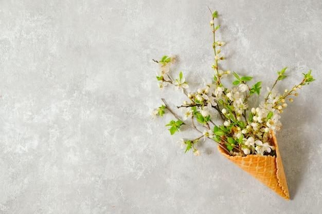 Rami di ciliegio in fiore in un cono di cialda su un tavolo grigio. vista dall'alto, copia dello spazio. primavera di concetto.