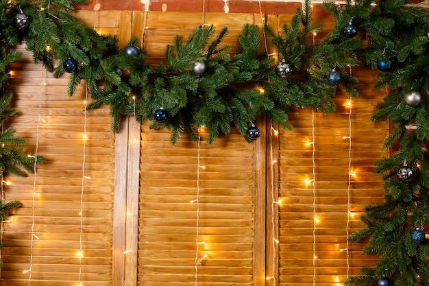 Rami di un albero di natale su uno sfondo di legno con i giocattoli di capodanno blu. addobbi natalizi per il soggiorno