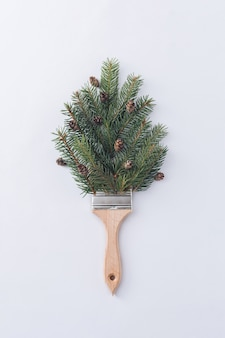 Rami di pino verde e un pennello su uno sfondo grigio. vacanze invernali e concetto di vacanze.