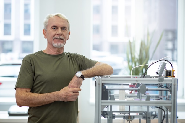 Dispositivo nuovo di zecca. uomo anziano ottimista che posa vicino a una stampante 3d e sorride mentre si appoggia il gomito su di essa