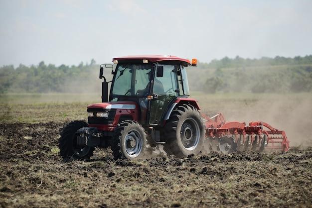 Nuovo trattore rosso sul campo di lavoro. trattore che coltiva il terreno e prepara un campo per la semina Foto Premium
